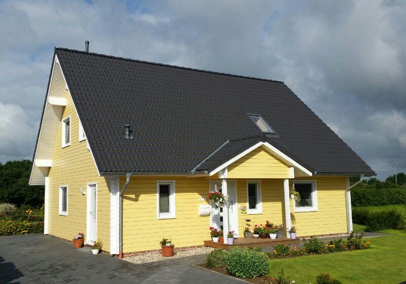 zweigeschössiges, gelbes Holzhaus
